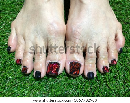 Nails art. Woman's feet with black nail varnish. Red foils and roses nail designs. Spring Summer. Barefoot on green grass background.