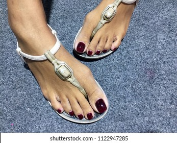 303dddeb09e2 Pedicure design nails burgundy. Feet with long manicured nails colored with  dark