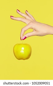 Nails Design. Female Hands With Colorful Nails Holding Apple On Yellow Background. Close Up Of Woman Fingers With Fashion Purple Manicure Holding Yellow Apple. High Quality Image.