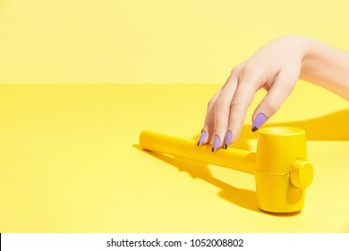 Nails Design. Hand With Colorful Nails On Yellow Background. Close Up Of Female Hands With Beauty Bright Geometric Manicure And Colored Hammer On Yellow Background. High Quality Image.