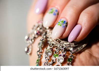 Nails Design. Hands With Bright lilac and White Manicure with Spring flowers. Close Up Of Female Hands. Art Nail.