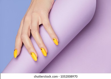 Nails Design. Hands With Bright Yellow Manicure On Violet Background. Close Up Of Female Hands With Trendy Orange Nails On Purple Background. Art Nail. High Quality Image.