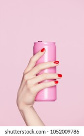 Nails Design. Red Manicure On Woman Hands. Close Up Of Female Hand With Soft Skin And Red Nail Polish Holding Pink Soda Can On Pink Background. High Resolution.