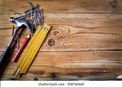 Nails, hammer,  pencil and folding meter on wooden background
