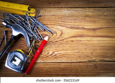 Nails, hammer, roulette, pencil and folding ruler on wooden background