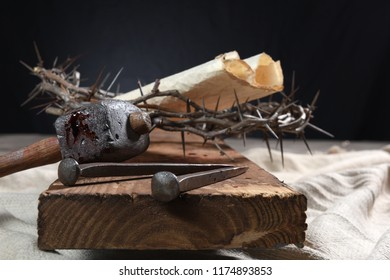 Nails, mallet, crown of thorns and parchment paper on cross