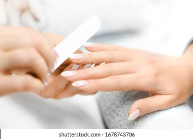 Nails manicure detail with file or brush item. Woman beautiful nail care process.