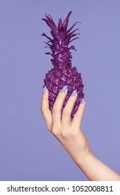 Nails Manicure. Hand With Stylish Nails Holding Purple Pineapple On Violet Background. Close Up Of Woman Hands With Smooth Skin And Bright Manicure Holding Colored Fruit. High Resolution.