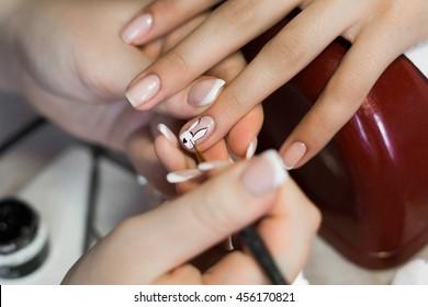 Nails saloon woman applying nail design