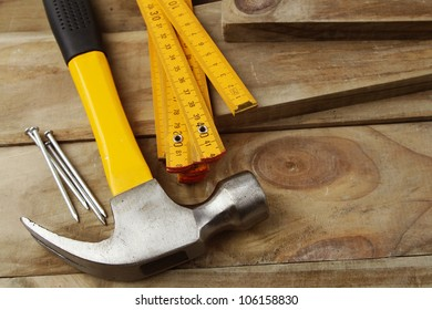 Nails,hammer and folding ruler on wood
