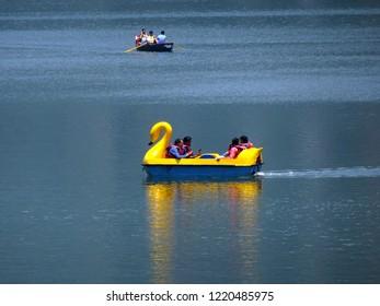Nainital, Uttarakhand / India - 26th May 2018 : Tourist people sailing yellow duck shaped rented paddle boat in Nainital lake water and enjoying vacation