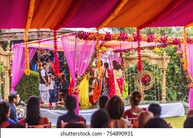 Nairobi, 14 Aug 2017: View looking through canopied tent toward raised platform where Indian pre wedding ceremony is underway. Bright colorful swathes of sheer fabric, roses and marigolds are visible.