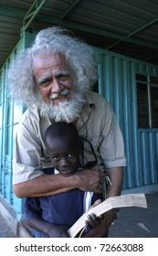 NAIROBI, KENYA - CIRCA MARCH 2008: Father Kizito embraces Brian 8 ages circa March 2008 in Nairobi, Kenya. Father Kizito Comboni missionary work in Kenya,founder of the Koinonia that collects abandoned children of Nairobi