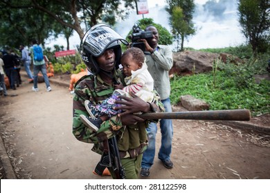 Nairobi, Kenya - February 13, 2014: A Kenyan riot police officer carries a baby during a protest.