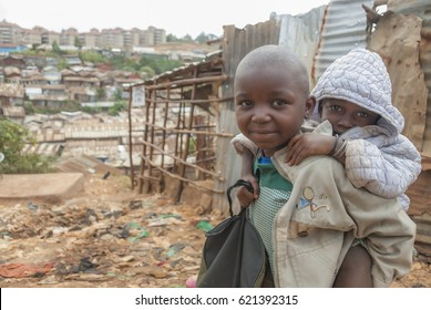 NAIROBI, KENYA - FEBRUARY 29: Unidentified boy carries his brother on street in Kibera, Nairobi, Kenya, February 29, 2012. Kids in Kibera have to care of their youngest instead of studying at school.