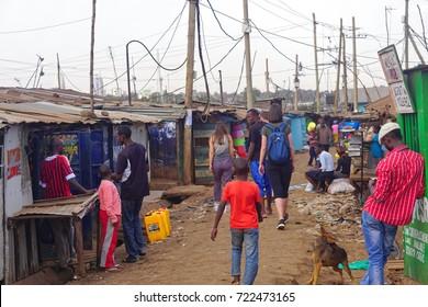 Nairobi, Kenya - July 10, 2017: Tourists and locals walking at street of Kibera slum in Nairobi, Kenya.
