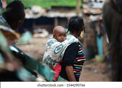 Nairobi, Kenya, May 2018: Portrait of a baby carried in a scarf on the back of his mother in Nairobi slum.