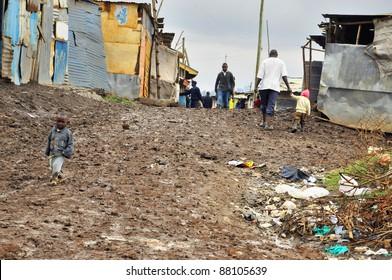 NAIROBI, KENYA  OCT. 13: Unidentified people walk in mud  through the Nairobi slum Oct. 13 2011 in Nairobi, Kenya. Kibera is the largest slum in Nairobi, and the second largest urban slum in Africa