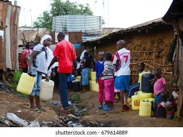 NAIROBI, KENYA - OCTOBER, 2016: Unidentified people walk in mud through the  Nairobi slum. Queue For Water to Kibera Slum Nairobi. Kibera is the largest slum in Nairobi.