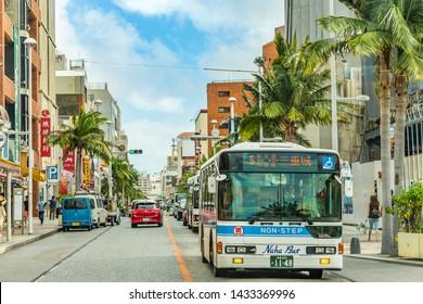 Nakagusuku, Japan - September 16 2018: Naha city non-step bus running through palm tree lined streets under Okinawa blue summer sky