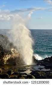 Nakalele blowhole in Maui, Hawaii outside of Lahaina with blue ocean background and lava rock. Sea water is forced through a hole in the rock shooting water high into the air.