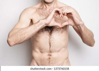 """naked adult man with a raised hairy torso posing on a white background. depicts finger symbol for """"heart"""". concept: the fight against heart disease and premature death of men"""