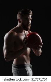 Naked athletic man with ball. stands sideways. isolated dark background