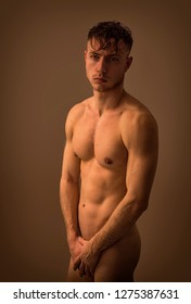 Naked Athletic Young Man After Taking Shower, Covering Groin with Hand, on Brown Neutral Background