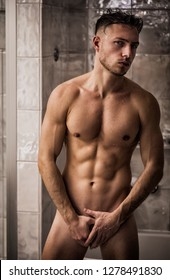 Naked Athletic Young Man After Shower in the Bathroom, Covering Groin with Hands and Looking at Camera
