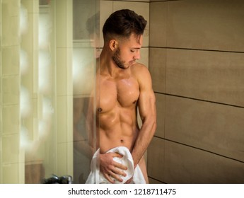Naked Athletic Young Man Taking Shower in the Bathroom to Refresh While Leaning Against Glass Door, Covering Groin with Hand