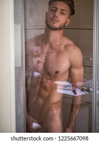 Naked Athletic Young Man Taking Shower in the Bathroom to Refresh While Leaning Against Glass Door, Covering Groin with Hand, Looking at Camera