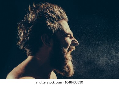 Naked bearded man angrily screams into a spray of water against a black background with copy space. Emotional portrait of a man like a barbarian. Toned image. from the side close