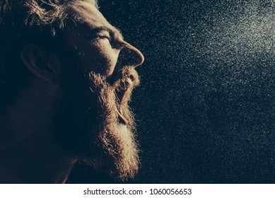Naked bearded man angrily screams into a spray of water against a black background with copy space. Emotional portrait of a man like a barbarian. Toned image. side view close up view