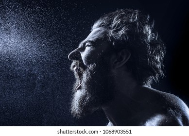 Naked bearded man angrily screams into a spray of water against a black background with copy space. Emotional portrait of a man like a barbarian. Toned image. side view close up