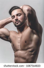 Naked bearded man looks at the camera. Portrait of strong healthy handsome Athletic Man Fitness Model posing near dark gray wall. Handsome young man with nude torso looking at camera