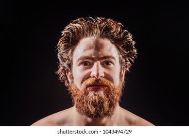 Naked bearded man is smiling in a spray of water against a black background. portrait