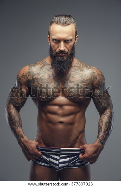 d24fe3c9c Naked bearded man with tattooed body standing on a grey background.