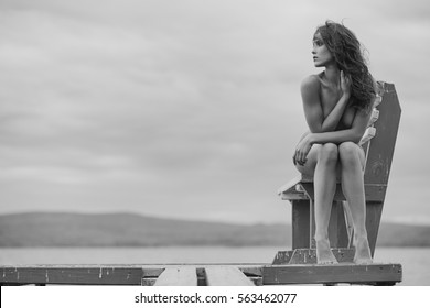 Naked beautiful woman on the nudist beach sitting on bench. Lady with nude perfect body. Lake beach with nude lady. Woman with perfect figure shows her nude body.