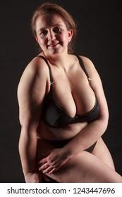 Naked beautiful woman posing on black background.