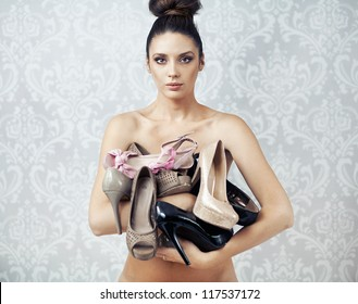 Naked beauty holding high heels