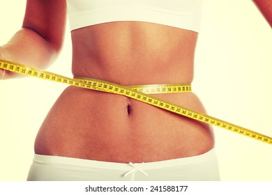 Naked belly of sexy, fit, young woman measuring her waist