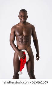 Naked Black Young Muscular Man Posing in Studio with White Background Covering Groin Area with Santa Hat and Looking at Camera