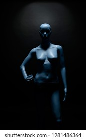 Naked blue plastic woman mannequin standing against black wall illuminated by light coming from above.