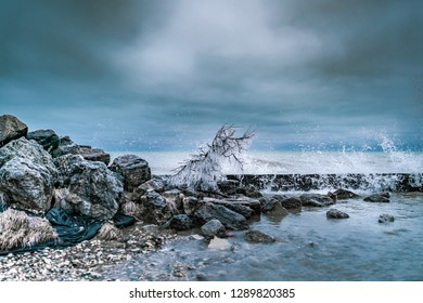 A naked branch covered in prickly icicles among the boulders and rocks on the Lake Michigan shore, droplets of water from crashing waves falling into the pool of water.