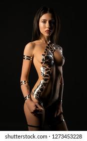 Naked brunette with gold tape bodyart shot