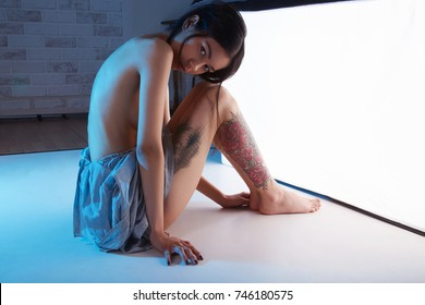naked brunette young woman.nude girl with tattoo in blue color studio