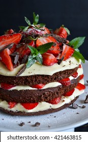 Naked cake with cream, decorated with strawberry, mint and chocolate on a black background