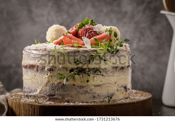 Naked cake with strawberries on kitchen counter top.