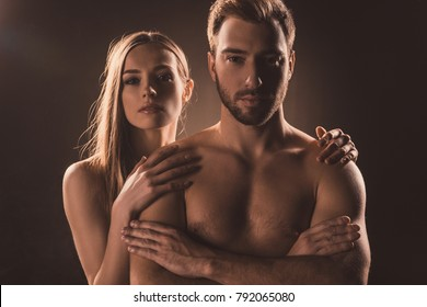 naked caucasian couple hugging and looking at camera