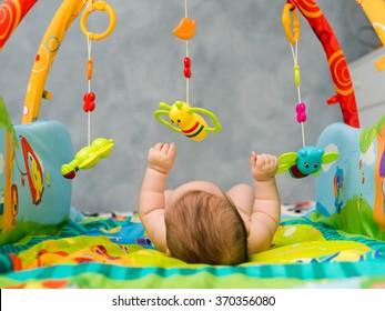 naked child playing lying on Developing rug